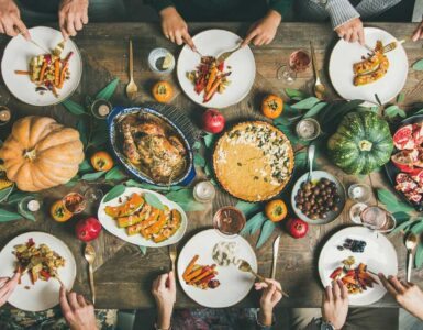 overhead photograph of six people sitting down adn eating a traditional thanksgiving dinner