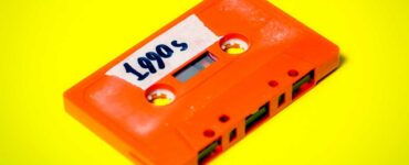 "orange cassette tape on a yellow background with a label that reads ""1990s"""