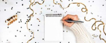 A woman's hand holds a pen, ready to write in a blank notebook surrounded by gold confetti