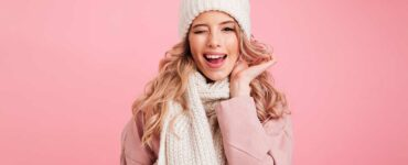 White blonde woman wearing a white hat and scarf along with a pale pink jacket in front of a pink background