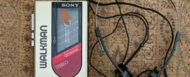 a walkman with wire headphones sitting on a beige rug