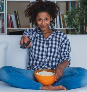 A woman holding a bowl of popcorn uses a remote control to change the channel