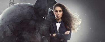 A long-haired woman in a suit stands stoically as a wrecking ball breaks against her shoulder