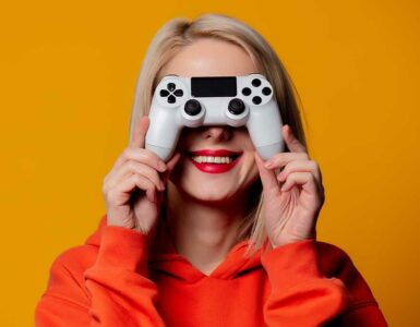 Happy blonde gamer girl holds controller in front of ther face