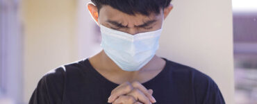 a young man wears a medical mask while he prays