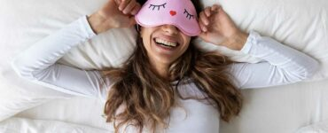 Lazy girl reclining in bed wearing an eye mask