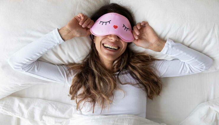 Lazy girl reclining in bed wearing an eye mask