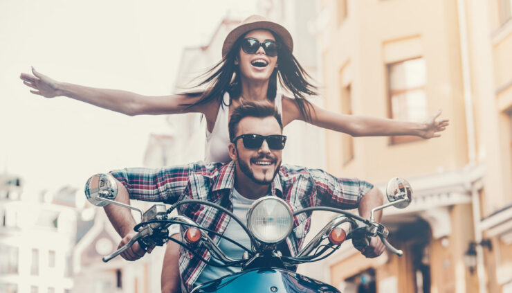 An attractive couple ride a motorcycle down a city street.