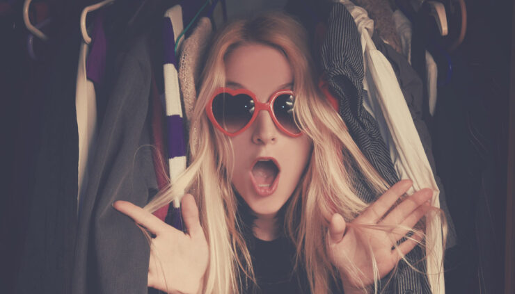 A blond woman with red heart sunglasses peeks out behind a cluttered closet of clothes.