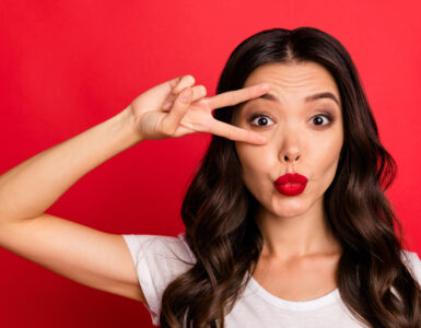 Beautiful brunette woman on a red background wears red lipstick and holds a v-sign around her eye.