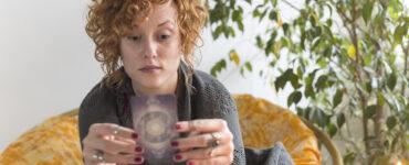 A redheaded woman reads a tarot card.