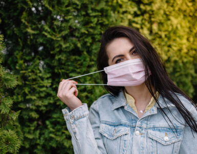 A brunette woman puts on a mask while walking in a park.
