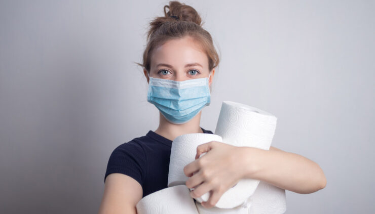 A woman in a mask holds an armful of toilet paper rolls.