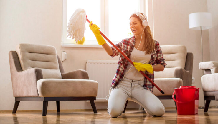 A woman in headphones dances with a mop while she cleans.