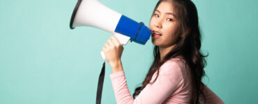 Asian woman holds a megaphone on a teal background.