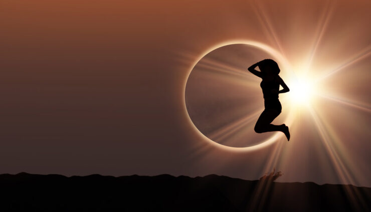 Silhouette of a woman jumping in front of a solar eclipse.