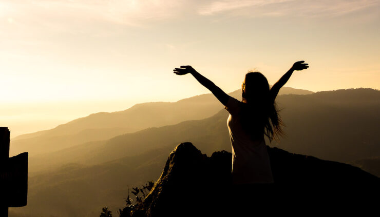 Silhouette of a woman standing on a mountain top with her arms upraised.