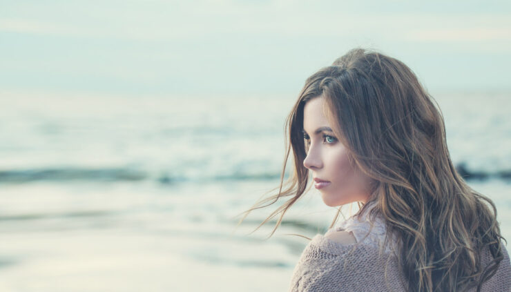 A woman looks dreamily over the ocean.