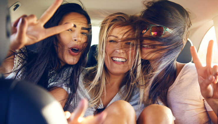 Three windswept girls riding in the backseat of a car flash peace signs at the camera.