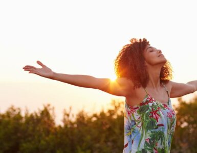 Beautiful African American woman raises arms in an open field at sunrise.