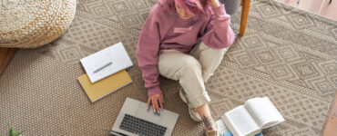 Pink haired girl works on her laptop on the floor.