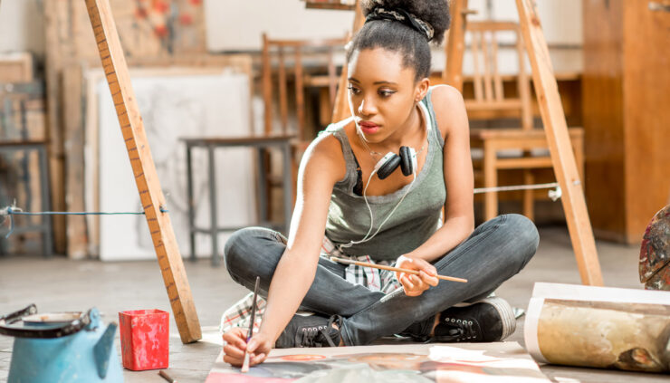 African woman surrounded by easels in art studio paints on the floor.