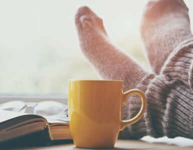 Feet wearing fuzzy socks next to a mug and a book.