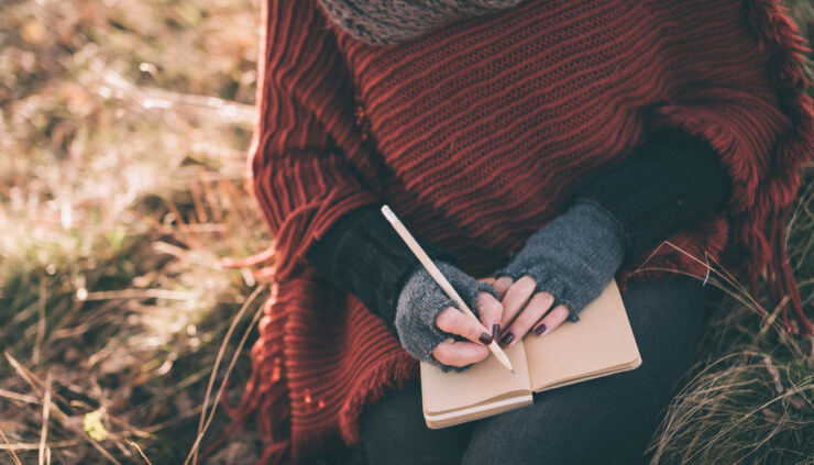 A woman in a sweater cape journals in a field.