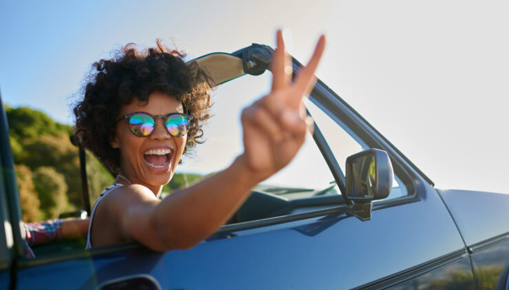 African American woman in a convertible flashes a peace sign at the camera