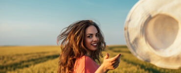 Woman in a field throws her hat at the camera.