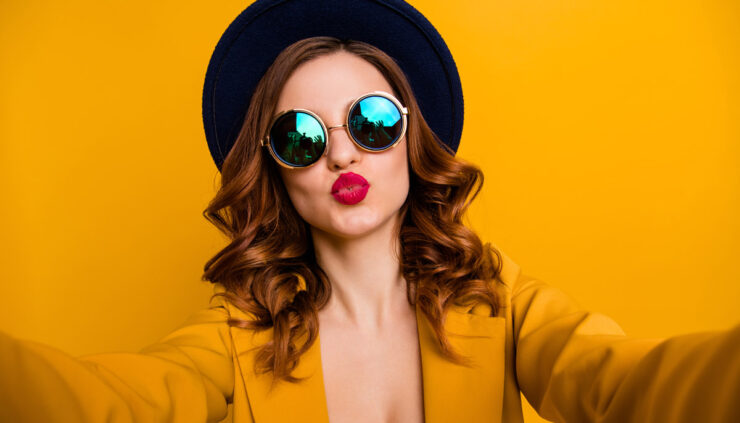 Red headed woman in sunglasses and red lipstick on a bright gold background.