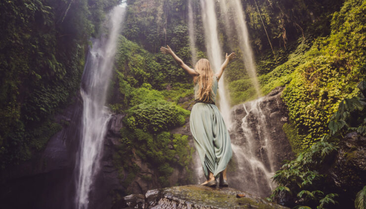 A woman in a turquoise dress standing on a cliff near a waterfall with her arms raised.
