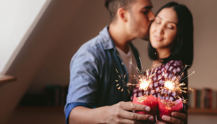 man-kisses-woman-on-cheek-while-they-hold-sparkler-cupcakes