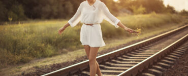 Young woman holding flowers balancing on a railroad beam