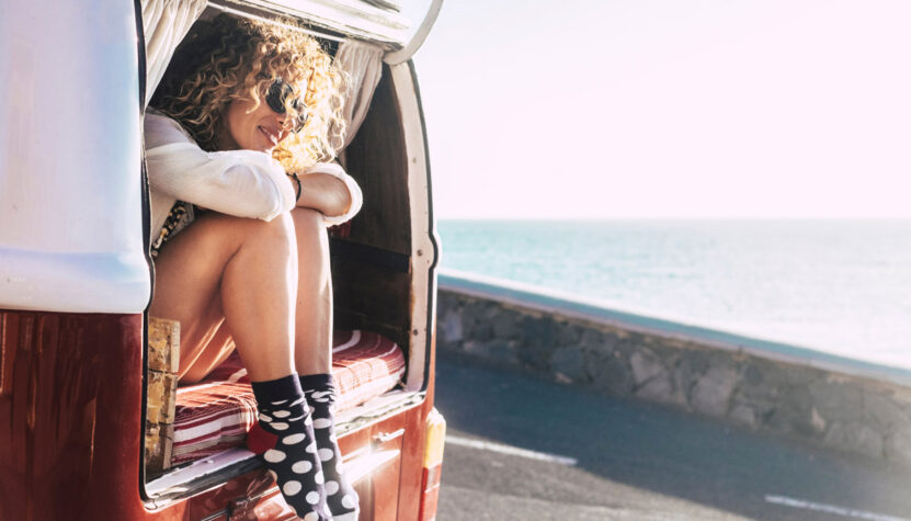 Woman sitting in a van by the ocean