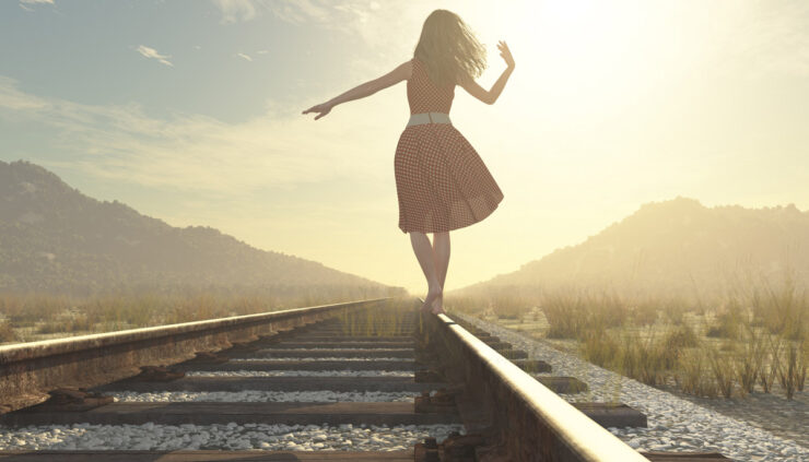 Woman balancing on railroad track