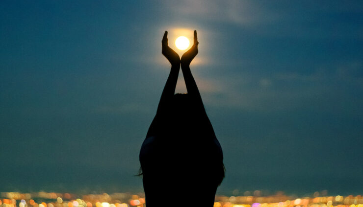 Woman with hands around moon