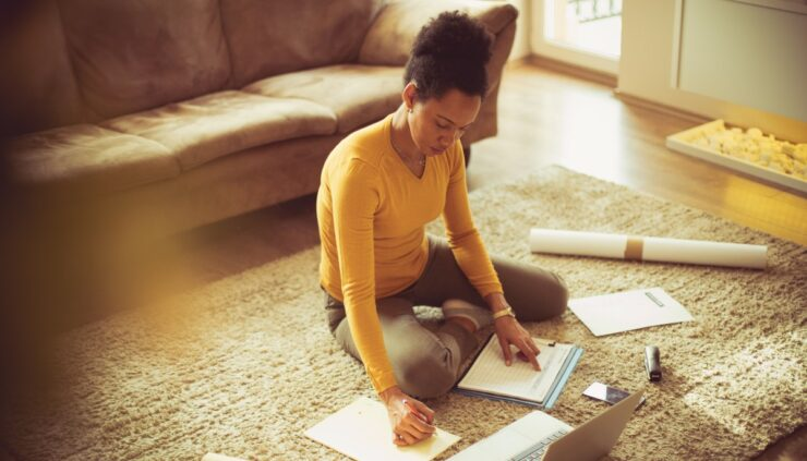 a woman sitting on the floor being productive