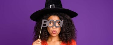 "Woman wearing a witch's hat and holding up a sign that says ""boo!"""