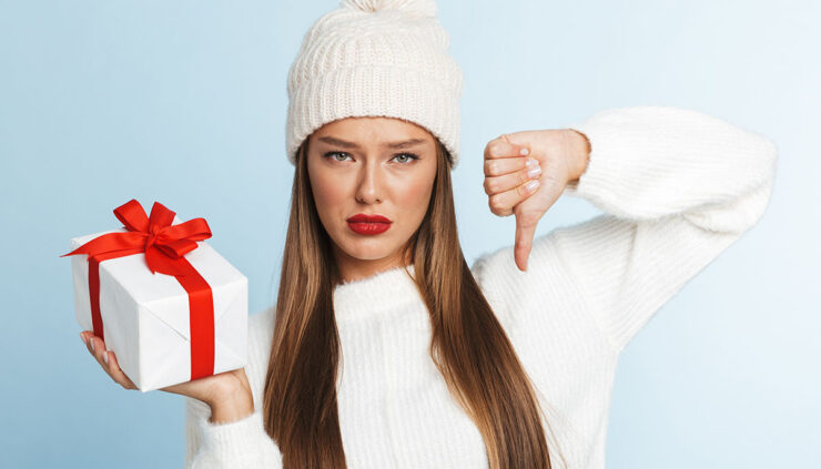 Woman giving a thumbs down because she does not like her present
