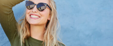blonde-woman-smiles-in-sunglasses-and-green-shirt