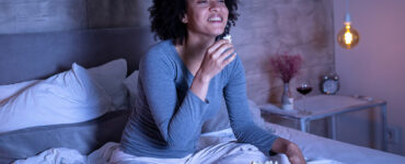 woman-eats-popcorn-and-laughs-in-bed