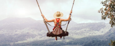 Woman on swing overlooking mountains