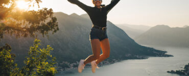 Woman on cliff jumping in air