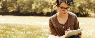 Woman in field journaling